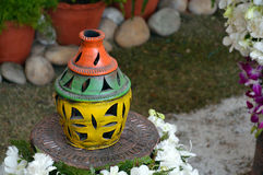 Colourful Earthen Vase. Handmade colourful earthen vase on a stand with flowers and flowerpots in the background, India, Asia Stock Images
