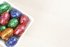 Colourful easter eggs in bowl. Colourful easter eggs in a white square bowl with a wood grain background Stock Photos
