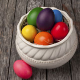 Colourful Easter eggs on wood. Brightly colored Easter Eggs in a pretty white bowl on a wooden table. Simple yet beautiful traditional decoration stock image