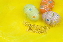 Colourful Easter eggs and yellow feathers Stock Image