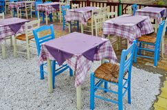 Colourful Greek island taverna Tables, Greece. Colourful empty and bare taverna tables with purple or mauve table cloths and blue painted wooden chairs with stock images
