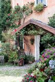 Colourful entrance of a countryhouse, decoration of many flowers. In many vases around the door stock images