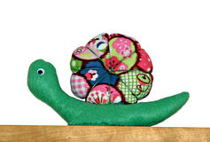 Colourful fabric snail. Photo of a very colourful fabric snail working his way along a wooden plank Stock Photo