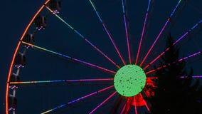 Colourful ferris koło na zmroku z drzewem w przodzie i - błękitny tło obraz stock