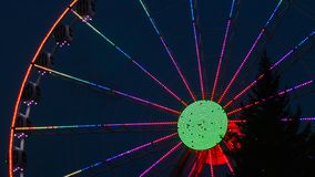 Colourful ferris wheel on a dark blue background and with a tree in the front of stock image