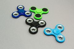 Colourful fidget finger spinner stress on grey background.  stock image