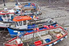 Colourful fishing boats and equipment at low tide Royalty Free Stock Images
