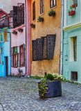 Colourful flower decorated vintage buildings. Old cobblestone street with pastel colored architecture in Sighisoara, Romania Royalty Free Stock Photos