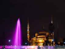Colourful fountain in front of illuminated mosque royalty free stock photo