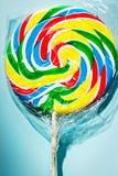 Colourful fruit lollipop. Swirl on blue background stock image
