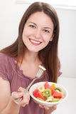 Colourful fruit plate. Beautiful young woman smiling and eating fruit salad, on white background stock photography