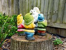 Colourful Garden Gnomes Standing on a Tree Stump. Colourful garden gnomes or dwarfs, aged from exposure in the garden, standing on a low tree stump royalty free stock photos
