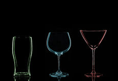 Colourful Glasses. A Red Martini Glass, a Blue Wine Glass and a Green Pint Glass on a Black Background stock photography