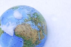 A closeup of colourful globe Earth covered in snow. A colourful globe Earth covered in snow, can be used as a concept for global warming stock photo