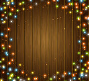 Colourful glowing Christmas garland, wood texture. Lights effects, luminous bulbs Royalty Free Stock Photography