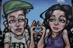 Colourful graffiti in Croydon, UK. Graffiti on a boarded up shop depicting a young couple looking sad with hearth shape fingers Stock Image