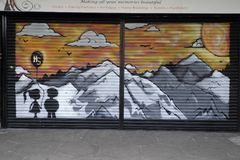 Colourful graffiti in Croydon, UK. Closed down shop with its shutter covered in colourful graffiti depicting a boy and a girl holding a balloon with mountains Stock Photography