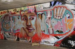 Graffiti decorating the skateboard area in the Undercroft,London,UK. Colourful graffiti depicting the face of a young man holding two half of a skaboard Royalty Free Stock Images