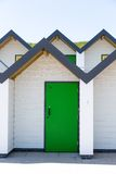 Colourful green door, with each one being numbered individually, of white beach houses on a sunny day Stock Photography