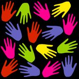 Colourful Hand Prints Background on Black. A background pattern featuring an assortment of colourful hand prints in pink, yellow, red, green and blue - fully Royalty Free Stock Images