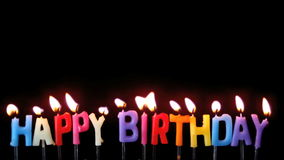 Colourful happy birthday candles being blown out on black background