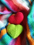 Colourful happy hearts. Red and green hearts on colourful stripe shawl freshen the merry day Stock Photo