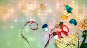 Colourful heart shape ribbon with small gift boxes on colorful bokeh, flare background. royalty free stock images