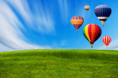 Colourful hot air balloons flying over green field. And blue sky Stock Images