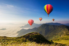 Colourful hot-air balloons flying. Over the mountain Royalty Free Stock Image