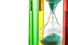 Colourful hourglass with green sand on white . Stock Photo