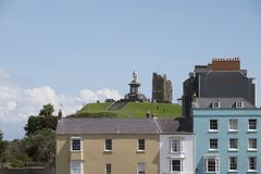 Colourful houses and Prince Albert monument in Tenby, South Wales. Pastel coloured houses in front of the Prince Albert memorial and castle in Tenby, coastal stock photo