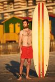 Colourful image of male surfer on beach with surfboard Stock Photography