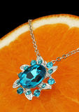 Colourful jewellery pendant with gems and diamonds on orange bac Royalty Free Stock Photo