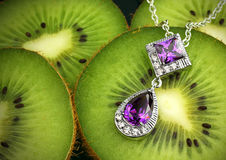 Colourful jewelry with gems and diamonds on kiwi fruit background. Jewelry with gems and diamonds on kiwi fruit background royalty free stock image