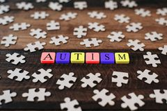 Colourful jigsaw puzzle and alphabet tiles with AUTISM word on wooden table. Autism concept Stock Photography