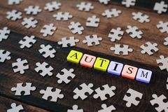 Colourful jigsaw puzzle and alphabet tiles with AUTISM word on wooden table. Autism concept Stock Photo