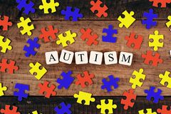 Colourful jigsaw puzzle and alphabet tiles with AUTISM word on wooden table. Autism concept Royalty Free Stock Photo