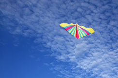 Colourful Kite in the fluffy sky Royalty Free Stock Image