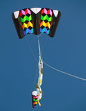 Colourful Kite flying in clear blue sky Stock Images