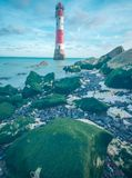 19/09/2018 Eastbourne, United Kingdom. Beachy Head lighthouse. Colourful landscape of the lighthouse during tide off and moss on the rocks royalty free stock photo