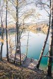 Colourful leaves on a footbridge, autumn, copy space. Autumn scenery: Footbridge and a blue lake, colourful laves footbdrige landscape leaves beautiful dock royalty free stock photo