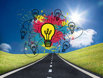 Colourful light bulbs graphic on bright countryside Royalty Free Stock Photos