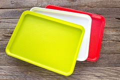 Colourful luncheon plastic square food plates on wooden backgrou Stock Photos