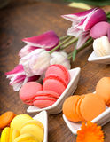 Colourful macaroons and tulips on table Stock Images