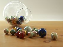 Colourful marbles rolling out of a glass jar on a table top stock photos