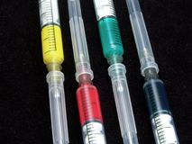 Colourful medical syringe. A colorful medical syringe with blue, yellow, red and green medication Stock Photos