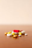 Colourful Medicine Pills. Lying on the table red white yellow orange big and small pills Stock Photo