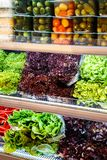 Colourful mix of different red, orange, yellow, green fresh and canned vegetables and greens at the shelfs of supermarket royalty free stock images
