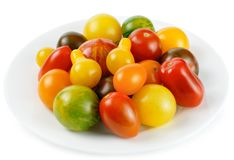 Colourful mix of different tomatoes. Different sorts of tomatoes served on a white plate, isolated on white background royalty free stock images
