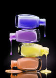Colourful nail polish dripping from many open bottles on black background. Close up Royalty Free Stock Photos